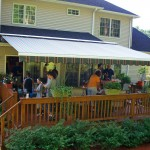 Family entertaining beneath a retractable awning on their porch.