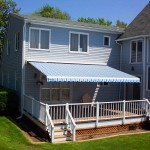 Blue striped retractable awning shading a porch.